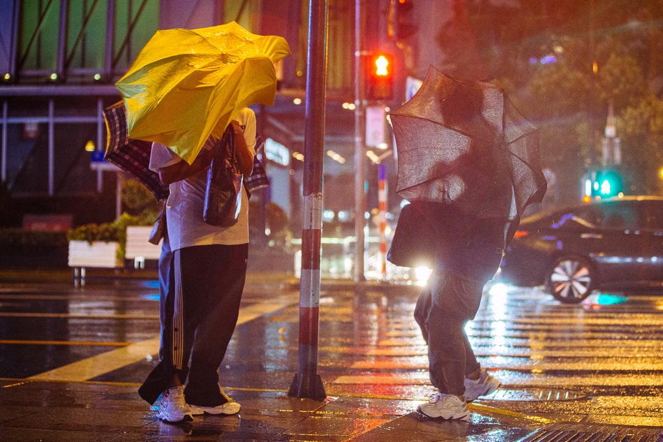 2021年9月13日,上海,河南路宁波路路口,行人的伞被风吹飞。