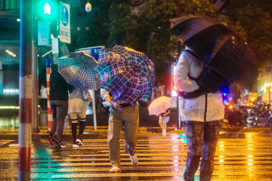 2021年9月13日,河南路宁波路路口,市民在风雨中出行。