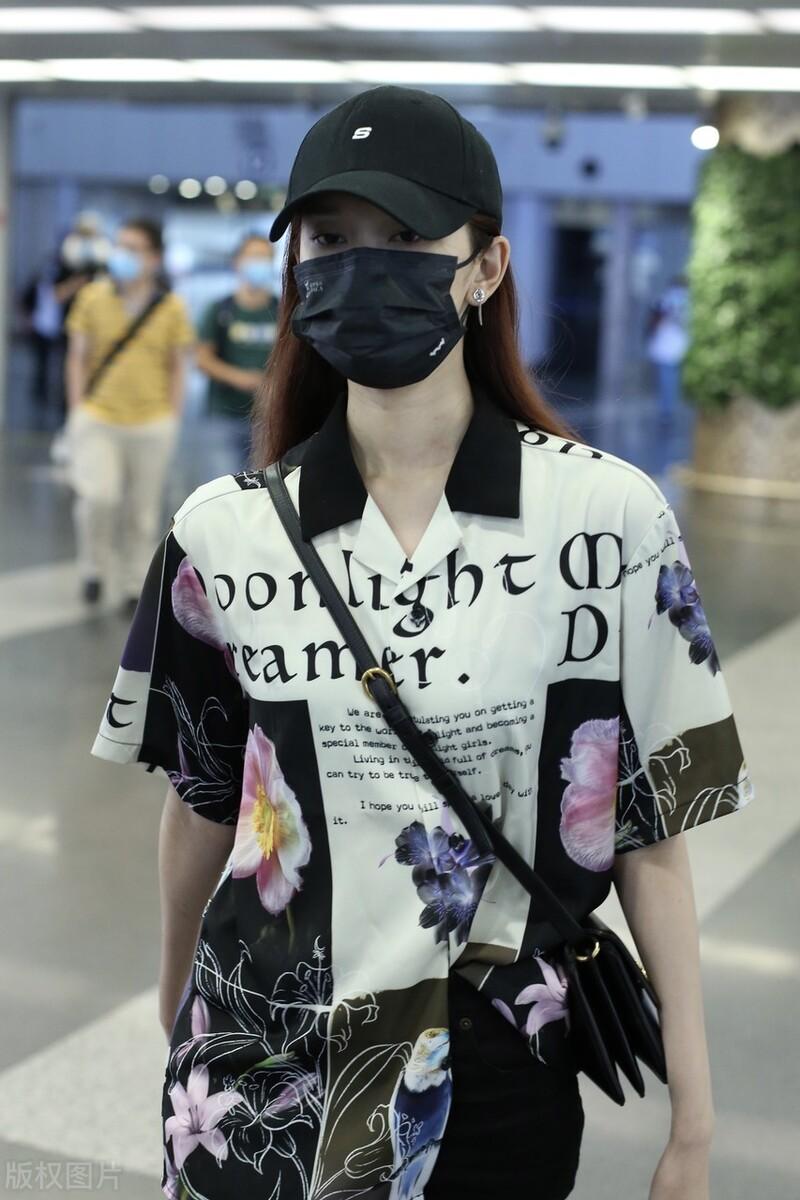 刘令姿穿印花衬衫搭配黑色打底裤,戴黑色棒球帽时尚干练