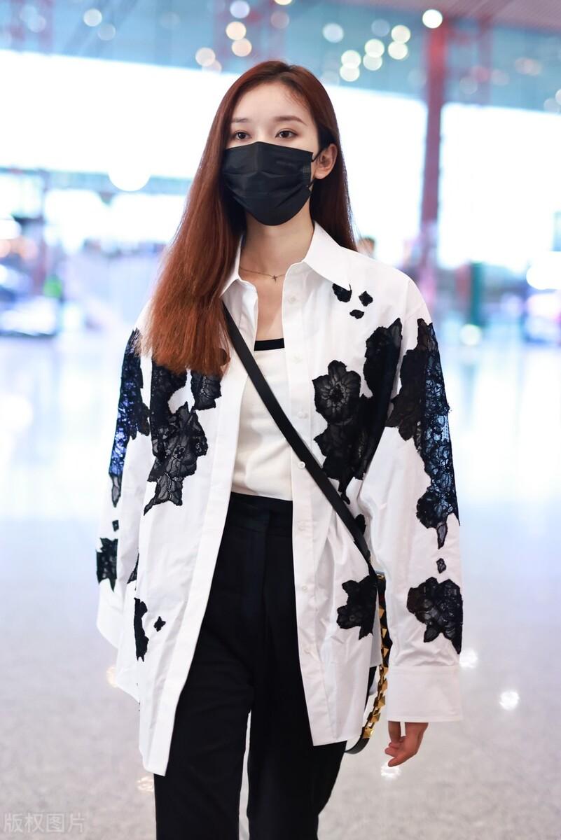刘令姿穿印花衬衫搭配黑色休闲裤,斜挎黑色皮质包精致时尚