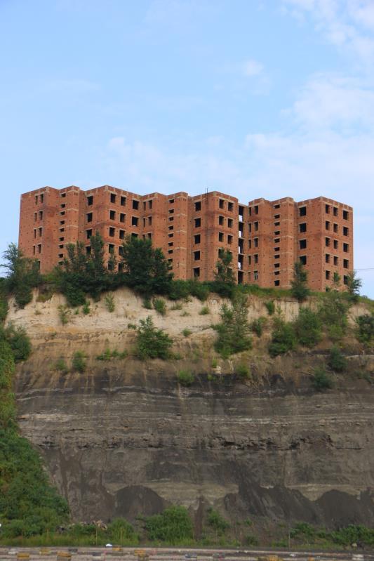 9月5日,举办草莓音乐节的废弃矿坑,黑色的煤层在山体上留下痕迹,上方有一处烂尾楼。新京报记者杜寒三摄