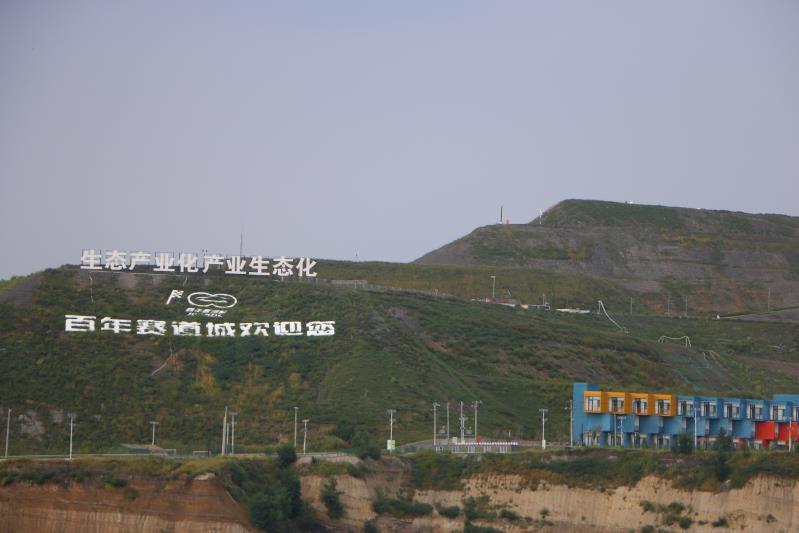 """9月5日,阜新百年广福娱乐网址赛道城,山头上立着""""生态产业化,产业生态化""""的标语。新京报记者杜寒三摄"""