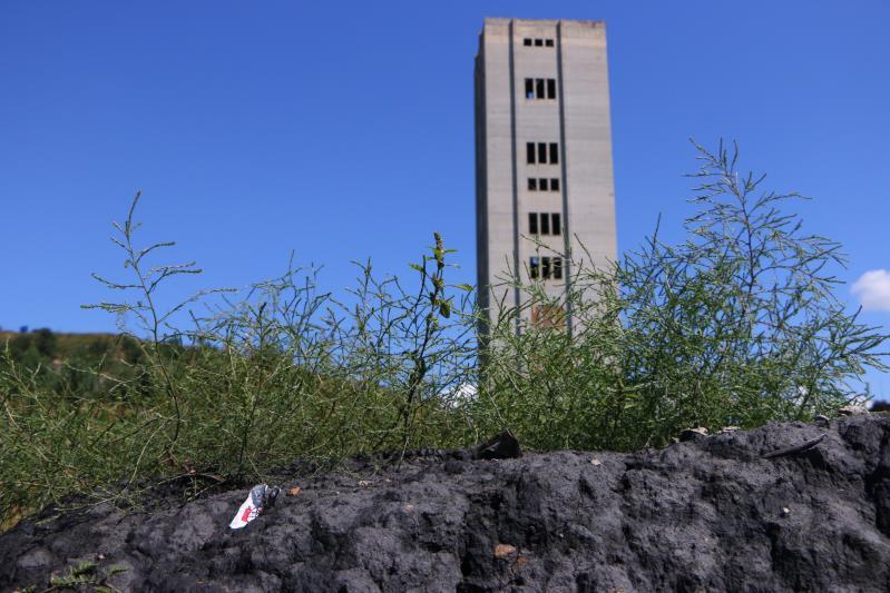 9月7日,阜新郊区一处废弃的竖井,围墙外堆着煤炭。新京报记者杜寒三摄