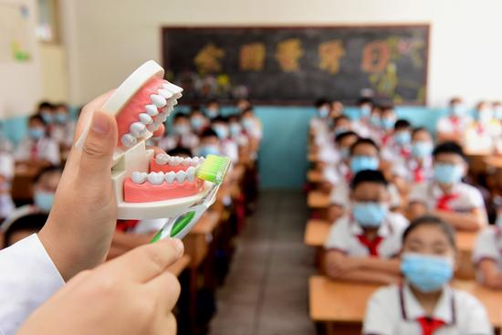 2020年9月18日,河北省石家庄新乐市实验小学,新乐市医院口腔医生指导学生学习正确的刷牙方法。视觉中国供图