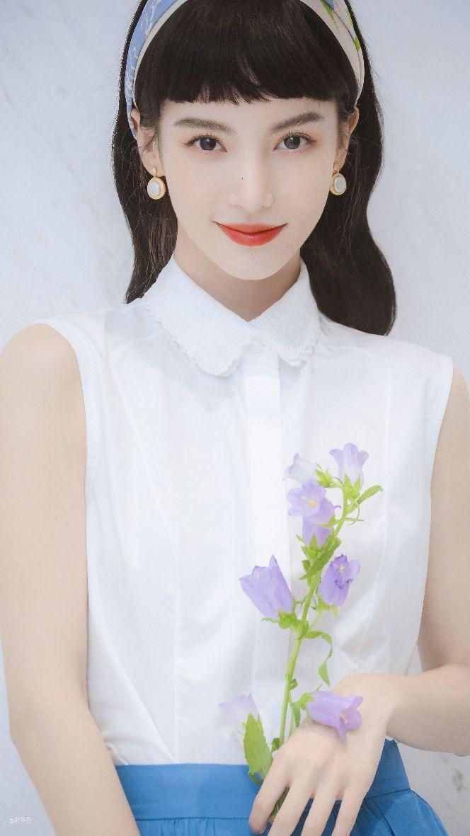金晨身穿白色无袖衬衫配水蓝色半裙,蝴蝶结点缀长发温柔可人