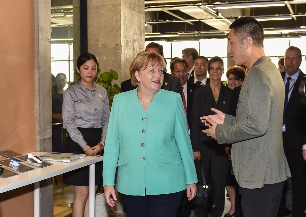 2018年5月25日,德国总理默克尔从北京飞抵深圳参观。这是默克尔(前左)在深圳本土初创型企业碳云智能科技有限公司参观。(新华社记者毛思倩摄)