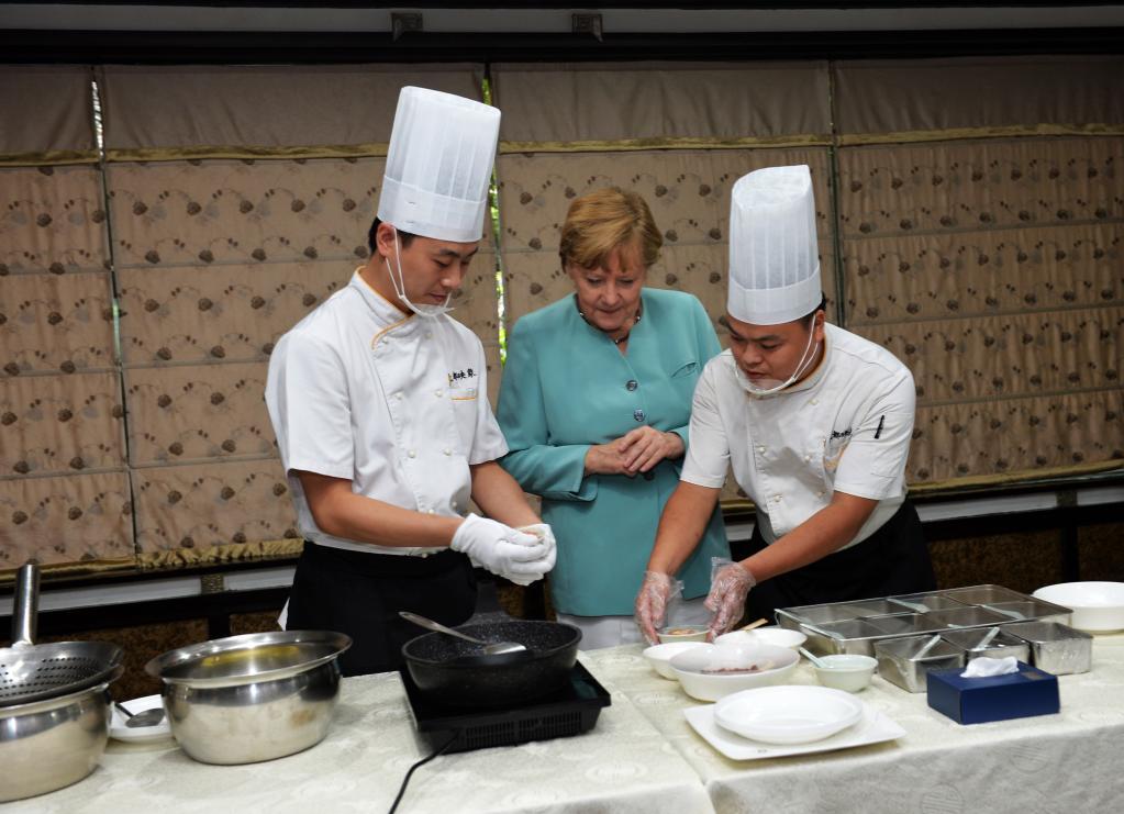 2014年7月6日,德国总理默克尔(中)在成都映象餐厅学习川菜宫保鸡丁的做法。(新华社发)