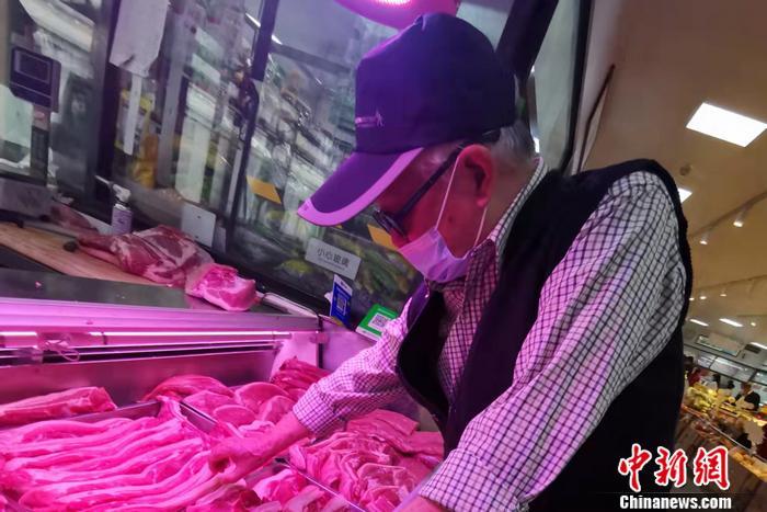 图为北京市西城区一家菜市场内,一位大爷正在挑肉。 中新网记者 谢艺观 摄