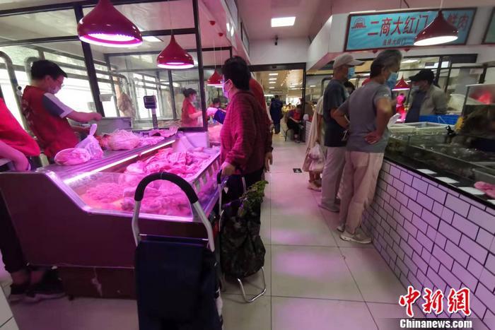 图为北京市西城区一家菜市场内,不少人正在买肉。 中新网记者 谢艺观 摄