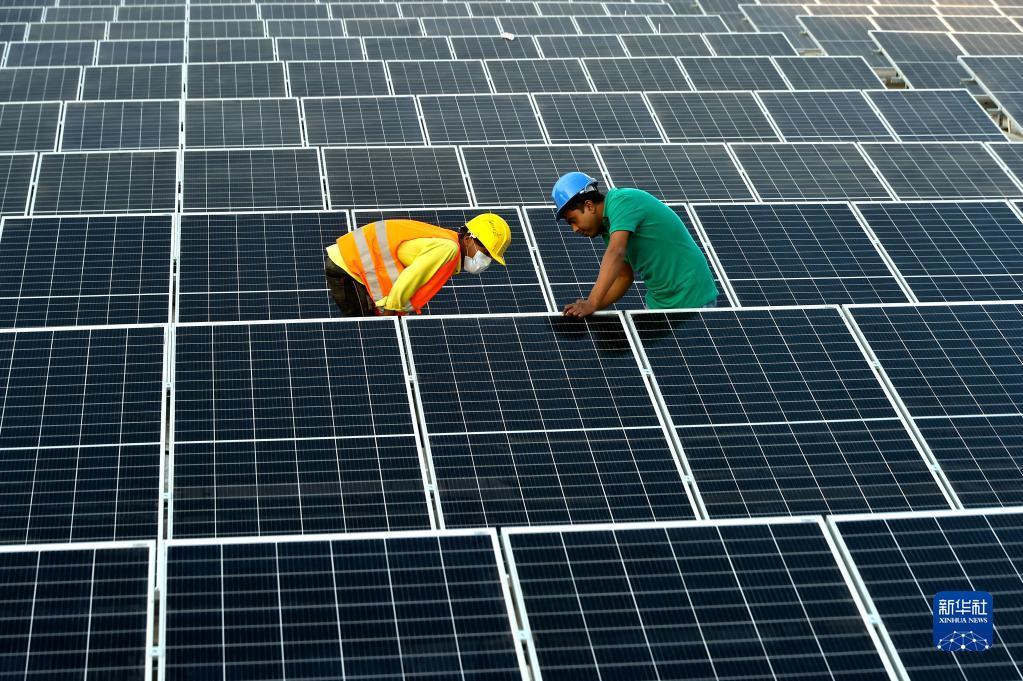 """2021年1月3日,在位于孟加拉国首都达卡郊区的利德成集团厂区,工人们在房顶组装光伏模组。从2020年开始,中资制衣类企业——利德成集团在其位于孟加拉国达卡的厂区内建设光伏电站,以降低对传统能源的依赖,减少碳排放,从绿色发展的角度助力""""一带一路""""建设。新华社发"""
