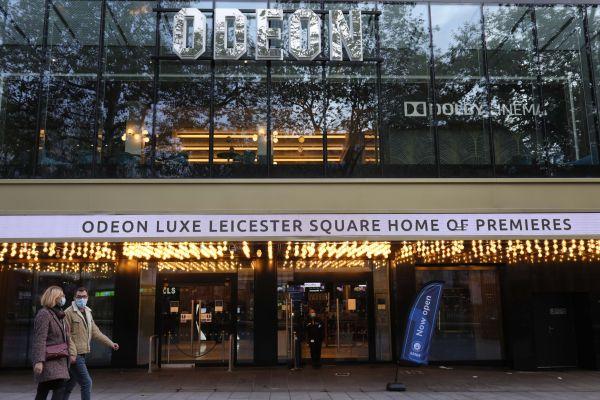 2020年11月1日,戴口罩的人们从英国伦敦莱斯特广场的一家电影院外走过。(新华社)