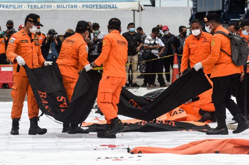 ↑1月10日,搜救人员在印度尼西亚雅加达戈戎不碌港搬运打捞起的失事客机遇难者遗体。