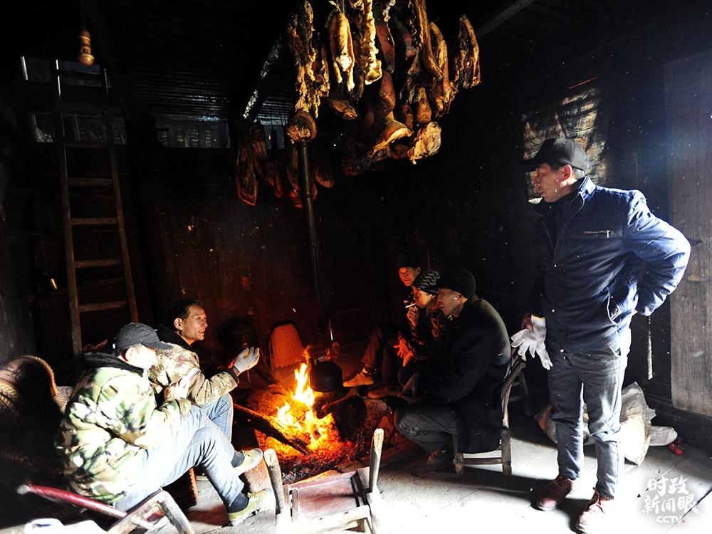 △渔山村村民在自家屋里熏制腊肉,围炉交谈。