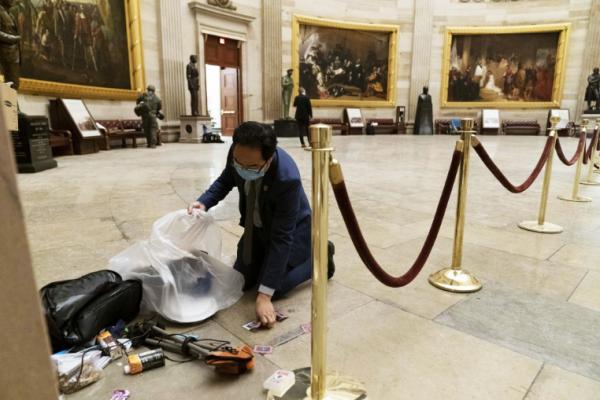 国会暴乱后,一位议员在大厅内捡拾遗留物品。图片来源:美联社