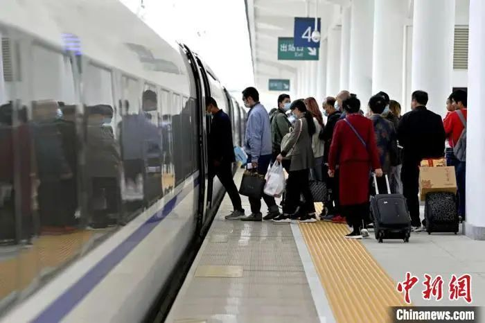 资料图:图为出行旅客正在有序排队上车中。王甜 摄