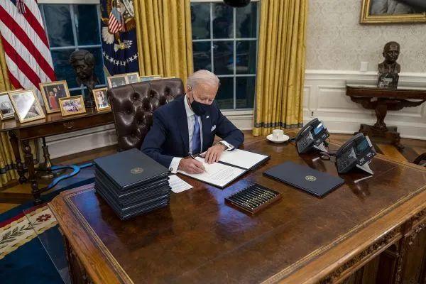 ▲资料图片:美国总统拜登1月20日在白宫椭圆形办公室签署行政令。(欧洲新闻图片社)