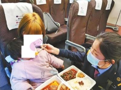 列车长蹲地十多分钟给母女俩喂饭