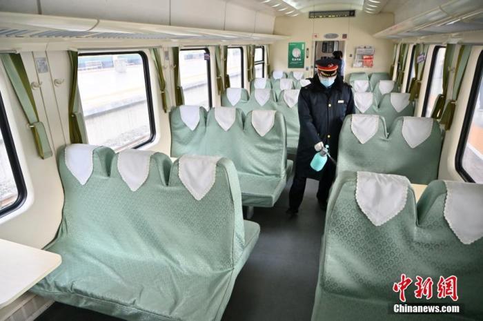 1月25日,内蒙古呼和浩特,列车员在火车车厢内喷洒消毒液。 中新社记者 刘文华 摄