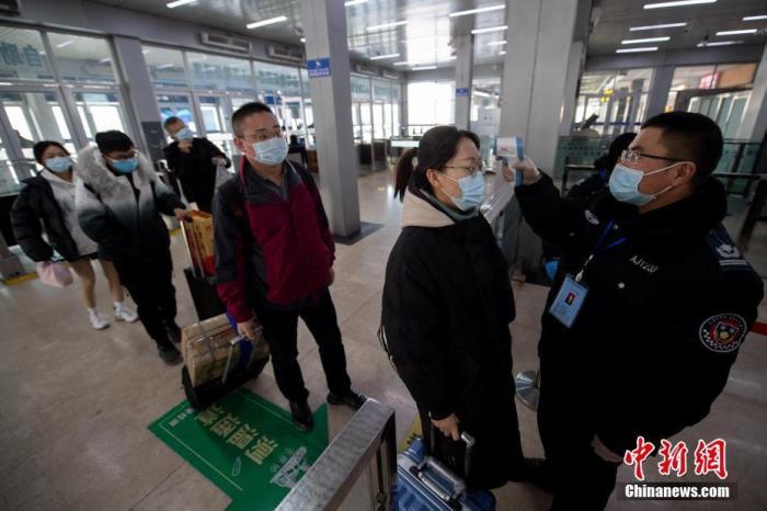 1月27日,山西太原站,工作人员为进站旅客测量体温。 中新社记者 韦亮 摄