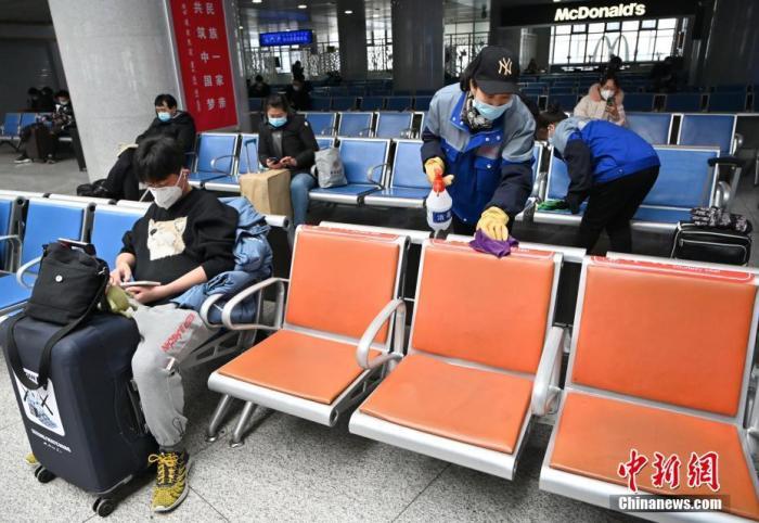 1月25日,呼和浩特火车站,工作人员在候车室内对座椅消毒。 中新社记者 刘文华 摄