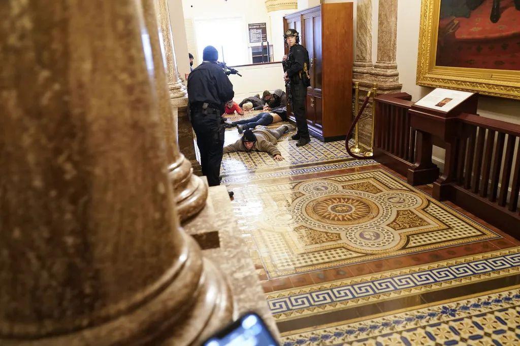 1月6日,示威者进入美国国会区域,并攻破了国会大厦。图为持枪警察控制示威者。图自澎湃影像