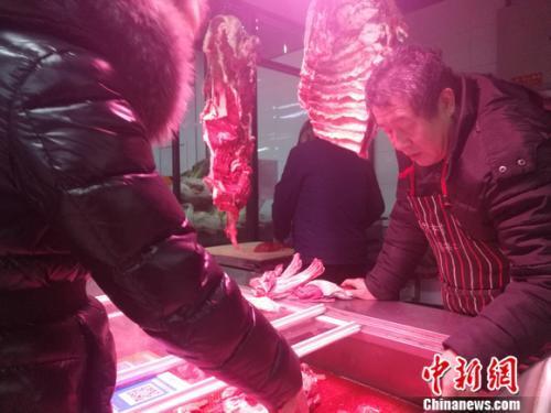资料图:北京西城区一家菜市场里的牛羊肉摊。 谢艺观 摄