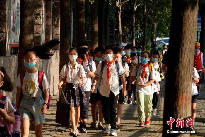 资料图:9月1日,河南郑州,长江东路小学的学生戴口罩有序进入校园。中新社记者 王中举 摄