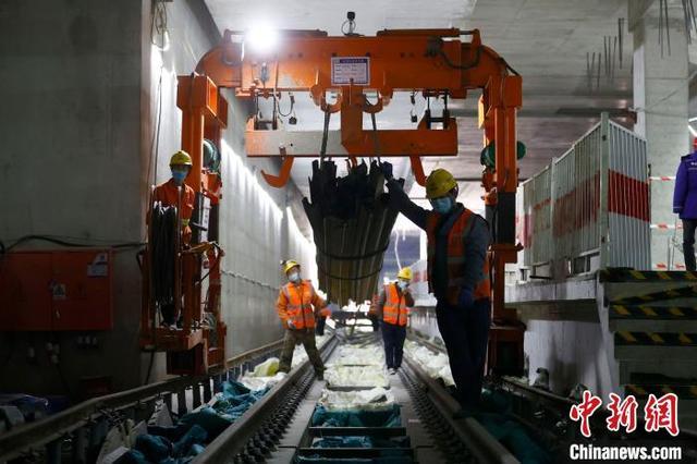 2021年2月23日,工人们正在北京地铁17号线南段隧道内进行钢轨铺设作业。 富田 摄