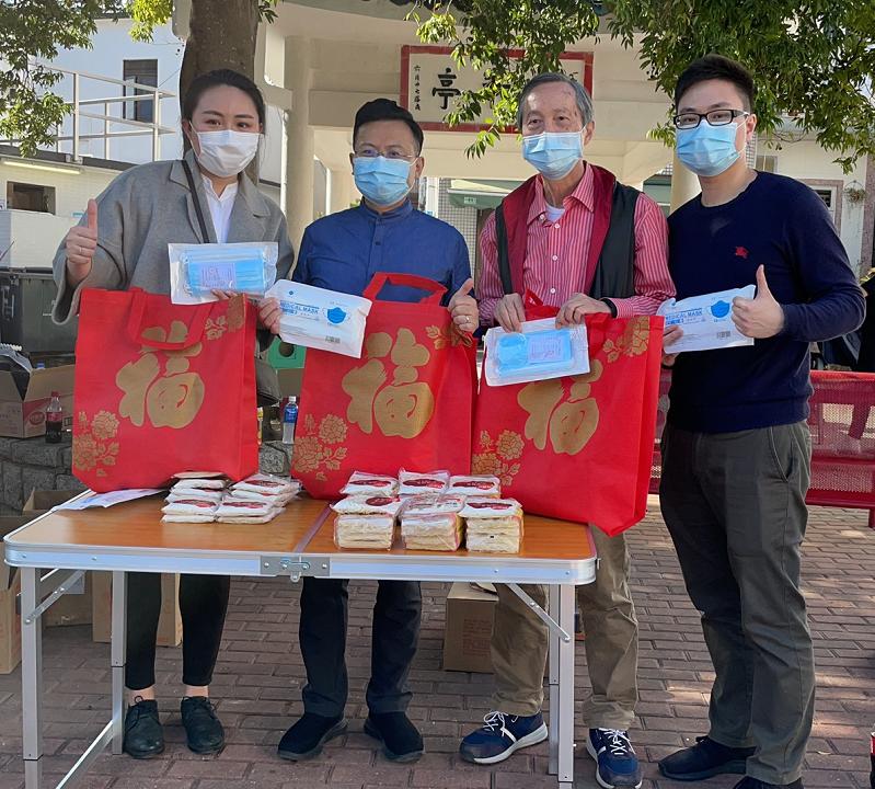 """陈勇与义工们向社区内老年人赠送包含口罩及食品的""""福袋"""""""