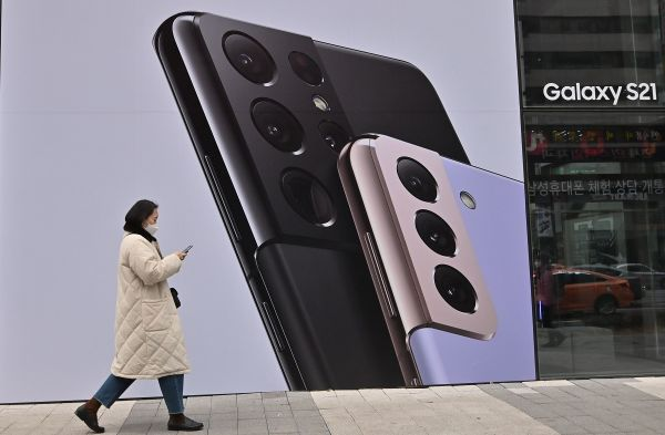 资料图片:1月28日,首尔街头一女子走过三星盖乐世S21智能手机的广告牌。(法新社)