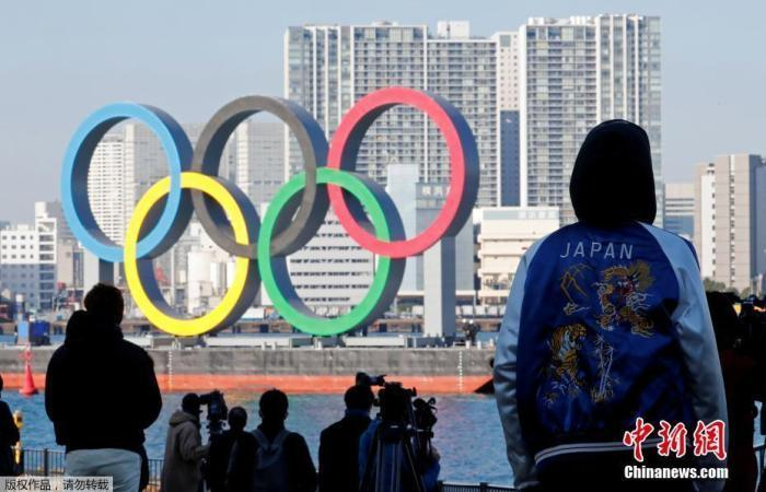 材料图;日本东京民众瞭望东京湾上的奥运五环标志、