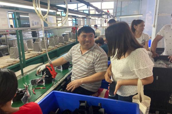 研究报告作者与带着一家5口人来广东打工的新疆柯尔克孜族工人(中间男子)在车间访谈 图自报告