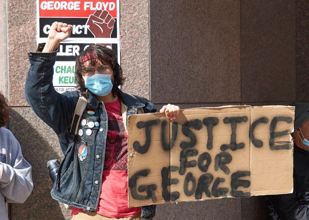 """美国示威者手举""""给弗洛伊德以正义""""标语参加抗议活动。图源:新华社"""