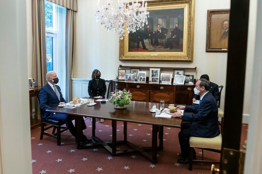 拜登与菅义伟16日一对一会晤,仅翻译在场,桌上摆着汉堡。图片来自拜登推特