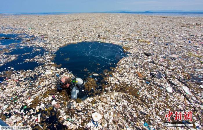 """资料图:摄影师Caroline Power在距离洪都拉斯罗阿坦岛仅有15英里远的海域拍摄到令人惊讶的""""塑料垃圾海"""",被污染的地区有近5英里,令人触目惊心。"""
