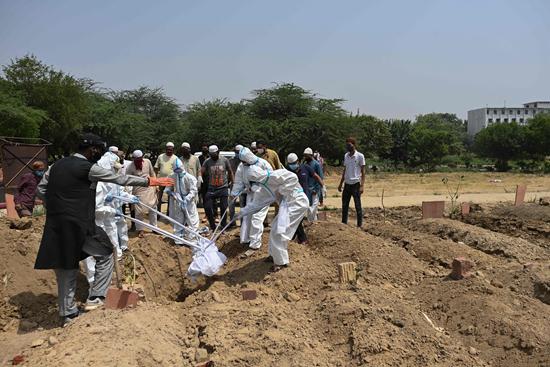 4月28日,人们在印度新德里安葬一名新冠肺炎死者。印度卫生部当日公布的数据显示,该国累计新冠死亡病例超过20万例。新华社/美联