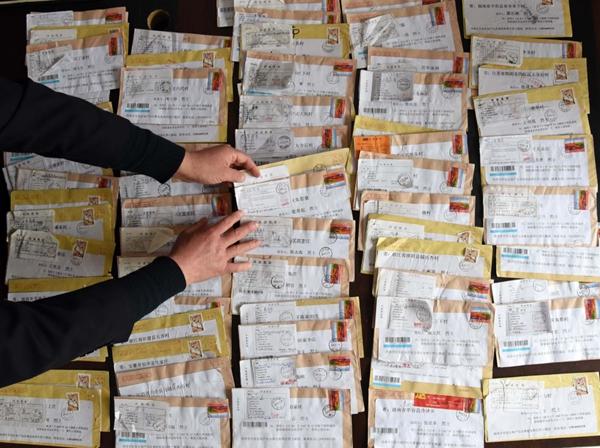↑2008年,时任山东省菏泽市张和庄村党支部书记的张景宪决心为张和庄烈士陵园的无名烈士找到家乡和亲人,告慰他们的英灵。从2014年开始,张景宪按照先前寻访到的资料地址,通过寄信等方式至今已为38位烈士找到亲人。这是2019年3月20日,张景宪在整理多年来他收到的退信。新华社记者王凯摄