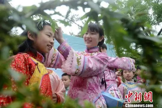 """资料图:图为清明节,扬州一景区开展""""插柳戴柳""""民俗文化活动。 孟德龙 摄"""