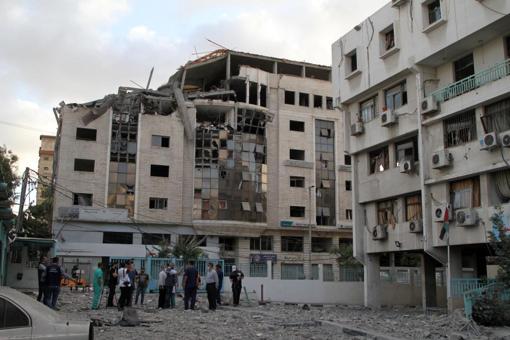 2021年5月17日,巴勒斯坦医务人员站在加沙城一处遭遇以色列空袭的医院外。新华社发(里泽克·阿卜杜勒·贾瓦德 摄)