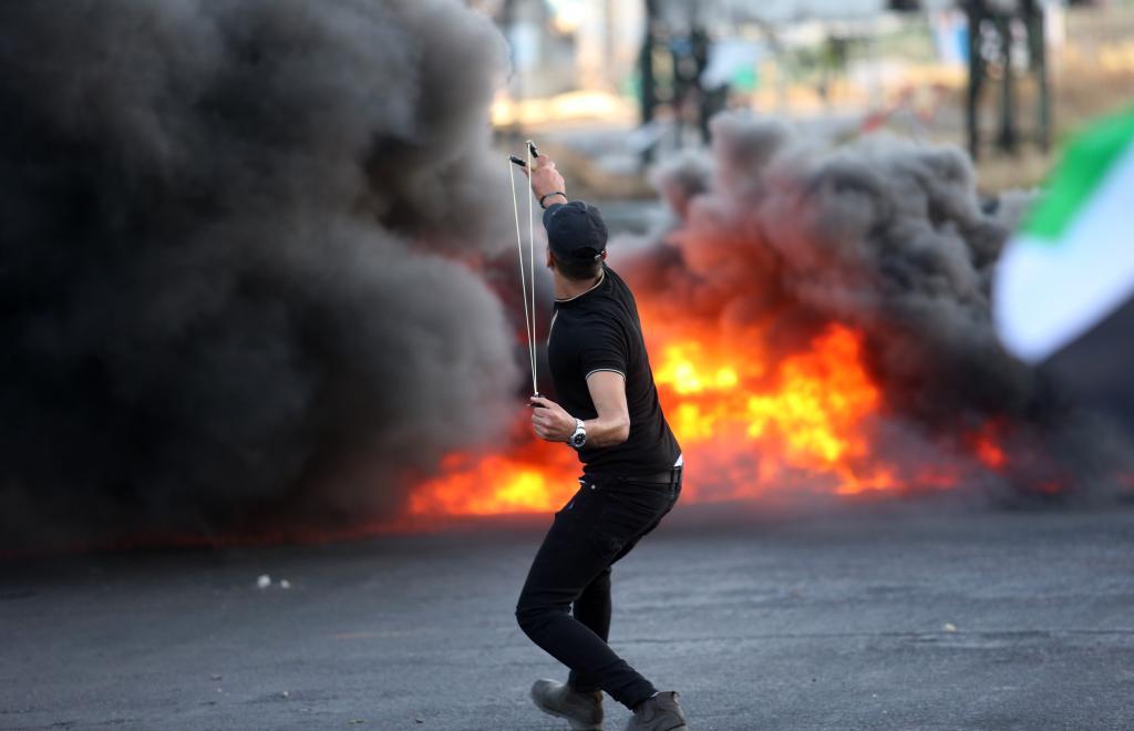 2021年5月17日,巴勒斯坦抗议者在约旦河西岸城市纳布卢斯附近向以色列士兵投掷石块。新华社发(尼达勒 摄)