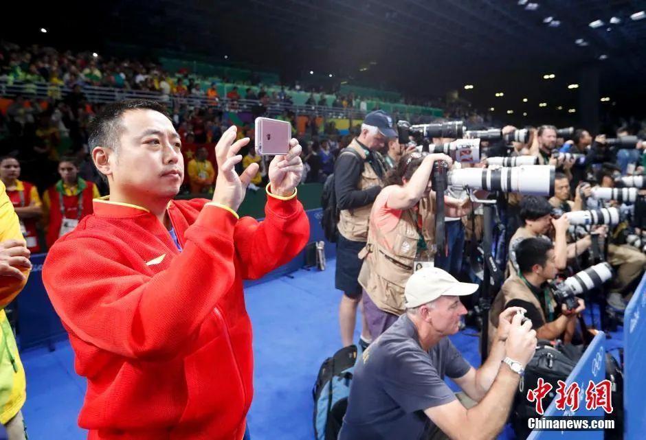 里约奥运会乒乓球男子单打决赛,马龙战胜卫冕冠军张继科夺得冠军,成为世界上第五个实现大满贯的男子选手。图为刘国梁用手机记录精彩瞬间。中新网记者 杜洋 摄