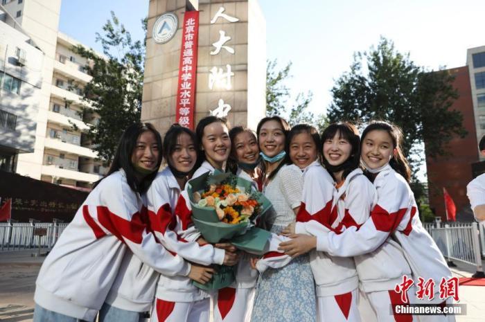资料图:6月10日,在北京人大附中高考考点外,考生们相拥拍照留念。当日,北京市2021年高考结束。 中新社记者 赵隽 摄