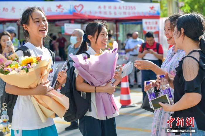 资料图:6月10日,海南省海口市海南中学考点外,家长为刚刚走出考场的考生送上鲜花。当日,海南省2021年高考结束 。 中新社记者 骆云飞 摄