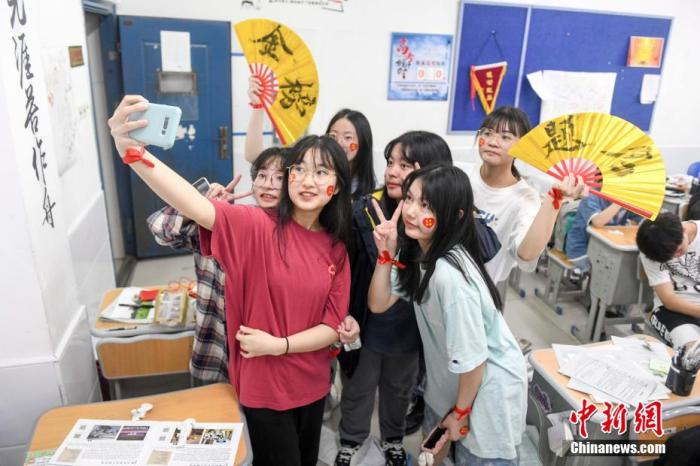 资料图:6月6日,2021年高考前夕,湖南长沙同升湖实验学校高三年级,考生们在教室内合影。 杨华峰 摄