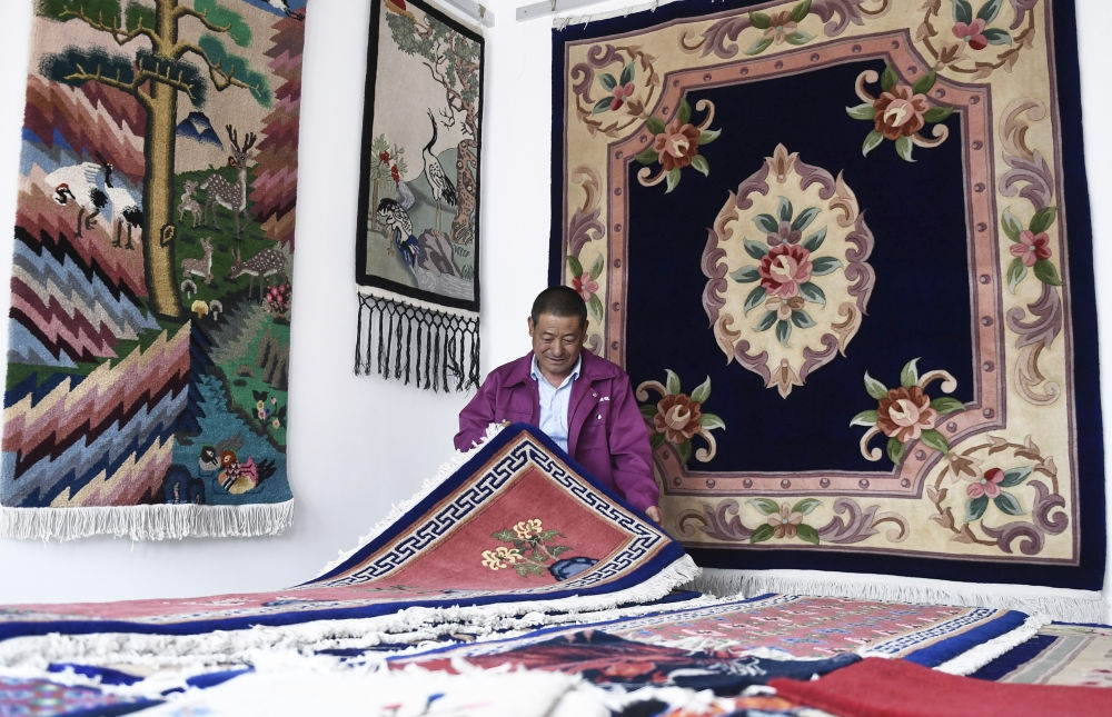 ↑6月5日,在西宁市湟中县加牙村,国家级非物质文化遗产项目加牙藏族织毯技艺传承人杨永良在整理制作好的藏毯。