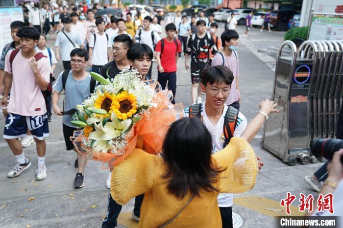 资料图:6月8日,广西南宁第二十九中学考点外,考生家长捧着花与考生拥抱。陈冠言 摄