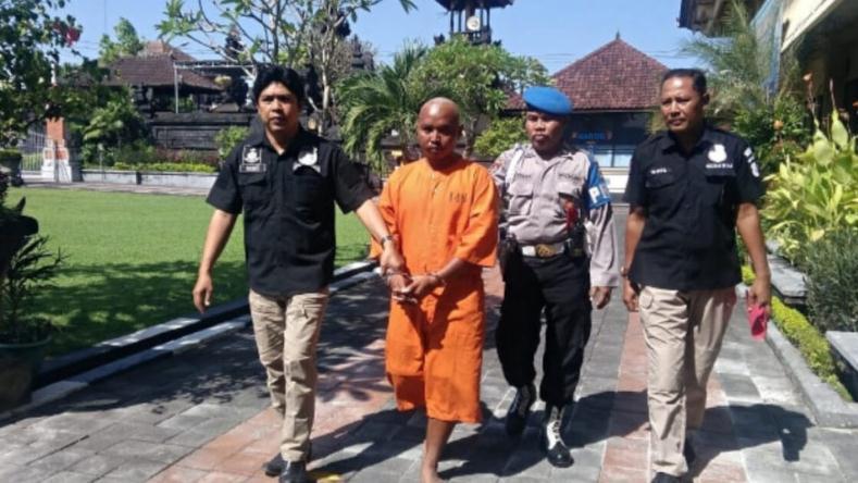 嫌疑人Toha(左二)身穿橙色监狱制服,在4月26日新闻发布会后被警察护送到监狱/图据detik新闻