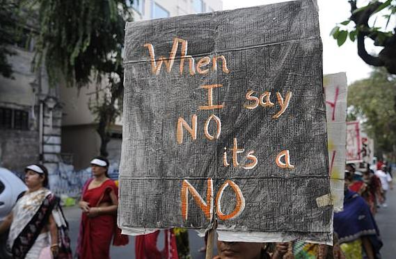 一名妇女在游行中举着牌子(图源:每日邮报)