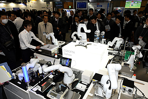 资料图:在日本东京,人们在展会上参观多种机械臂。(新华社)