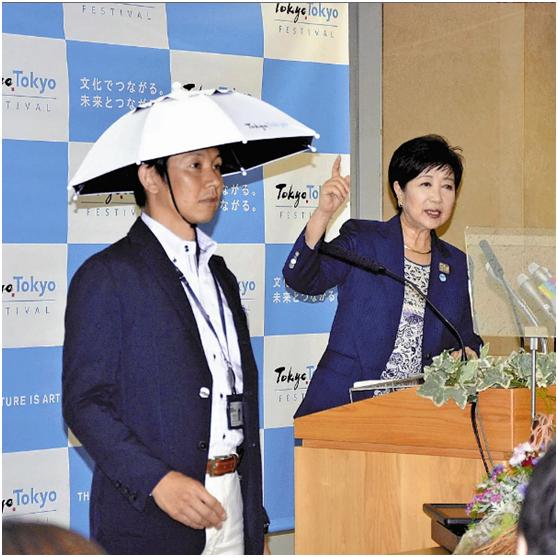 """东京知事小池百合子在发布会上介绍""""头戴式遮阳伞""""。图源:《读卖新闻》"""